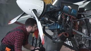 Man in uniform cleaning airplane engine in hangar