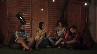 Man showing photo on smartphone to group of friends sitting on porch in evening