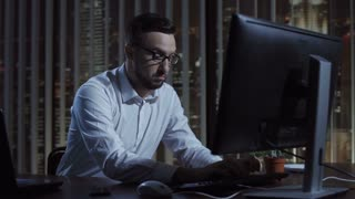 Man sitting and thinking while typing on computer in office at night