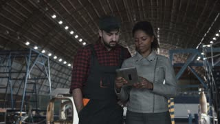 Man standing and discussing over digital tablet in aircraft hangar with woman