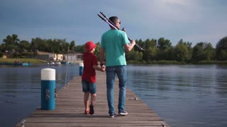 Mature father holding hand of son and walking on pier with rods. Then he sit and show on boats on the river