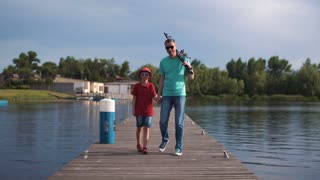 Mature man holding rods and walking with son on pier. Then he sit and show something on river. Wide view