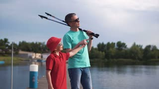 Mature man holding rods and walking with son on pier
