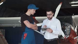 Mechanic and flight engineer having a discussion looking at a tablet-pc together as they stand in front of a small single engine aircraft in a hangar