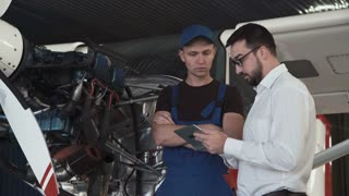 Mechanic standing near plane, looking at engine and talking to draftsman