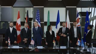 Members of Group of Seven taking photo against countries flags on international meeting in boardroom