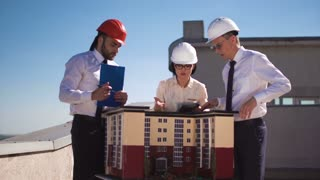Men and woman architects in hardhats and formal clothes standing and discussing at house model