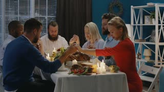 Men and women giving worship before starting delicious meal at table having Thanksgiving holiday celebration all together