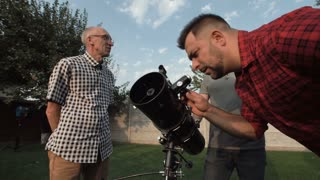 Men standing together on backyard and watching casual telescope