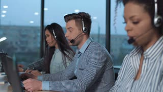 Men with headset working in call center in modern worldwide office he talking and looking on screen of desktop computer solving the client's problem