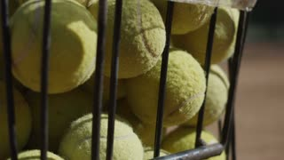 Metal bucket with yellow fluffy tennis balls on sports ground of tennis court in bright sunlight