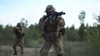 Military troop prepared for fight aiming with guns on the field