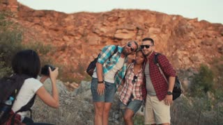 Mixed racial friends taking shot of three friends posing with backpacks while traveling together. Slow motion