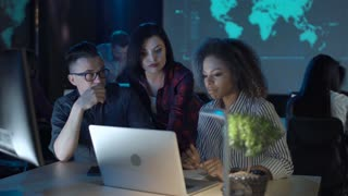 Mixed racial people working in modern office with low light interior, two women and man in front of computers discussing something