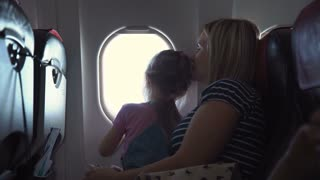 Mom and daughter on the plane looking out the window