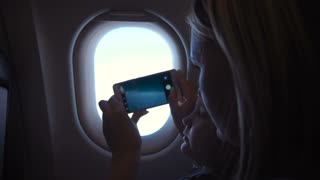 Mother and daughter taking shots with smartphone through illuminator in airplane