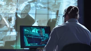 Movement shot back view of man working on space mission in control center. Elements of this image furnished by NASA