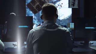 Movement shot back view of man working on space mission in control center. Observing the flight of a satellite in orbit. Elements of this image furnished by NASA