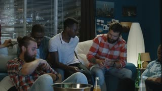 Movement shot of group of multiracial men on sofa at home making money bets for sport game while watching championship together
