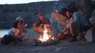 Movement stabilized 4K shot of group of multiracial people sitting around campfire grilling marshmallows and having fun on coast on lake