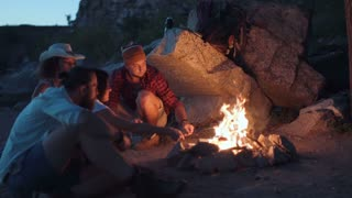 Movement stabilized 4K shot of group of multiracial people sitting around campfire grilling sausages and having fun on coast