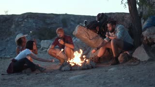 Movement stabilized shot of group of multiracial people sitting around campfire grilling marshmallows and having fun on coast on lake. Slow motion