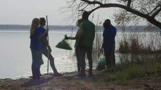 Multiethnic group of man and women working in volunteering union celebrating successful cleanup of nature on lake shore.