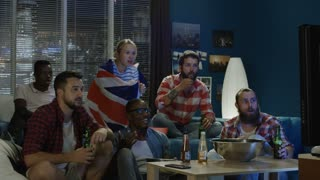 Multiethnic men and woman sport fans with British flag watching TV and having fail and unhappy with result