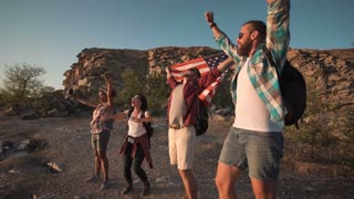 Multiracial group of people posing happily with American flag on point of destination celebrating