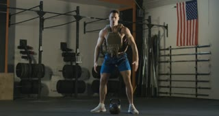 Muscular athlete wearing heavy weight vest and lifting kettlebell from floor working out hard.