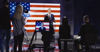 Official press conference of American representative politician on stage against display with American flag giving speech to audience in semilit studio. 4K shot on Red cinema camera