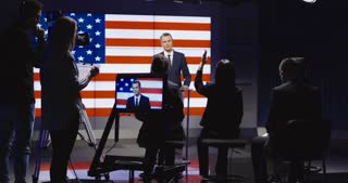 Official press conference of American representative politician on stage against display with American flag giving speech to audience in semilit studio and answers the questions