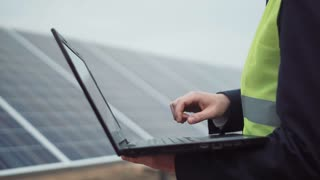 Outdoors crop shot of a person browsing the laptop on the solar panel site