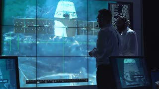 People in space mission control center managing spaceship undocking. Elements of this image furnished by NASA