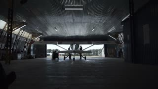 Person walking towards plane standing in hangar, view from behind