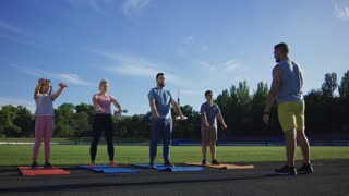 Personal instructor working with adult couple and children showing dumbbell exercise on green athletic field