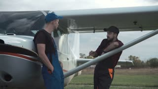 Pilot and mechanic chatting on an airfield as they stand together leaning on a small single engine plane