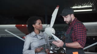 Pilot and mechanic discussing aircraft repairs or pre flight check standing in front of a small single engine aircraft in a hangar, male and female
