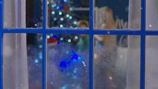 Playful little girl in Santa hat and boy standing near frozen window in Christmas night and having fun