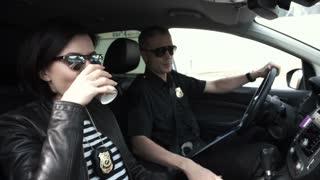 Policewoman with policeman relaxing in patrol car during break