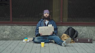 Poor bearded unemployed man begging in street with cardboard