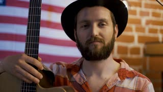 Portrait of cheerful bearded and tattooed man in hat holding guitar and giving smile at camera