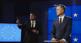 Producer and news anchor in a production team in a news studio issuing instructions while standing in front of the EU flag