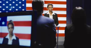 Production team filming a show host interviewing a group of people in a broadcast studio with an American flag backdrop