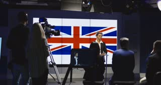 Production team giving instructions to a female news anchor as she stands in front of the British flag with a cameraman filming to the left. 4K shot on Red cinema camera