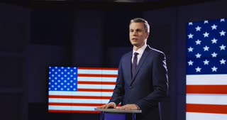 Public speaker or presenter in front of American flag standing at a small rostrum speaking and gesturing emphatically with his hands. 4K shot on Red cinema camera