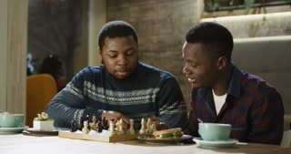 Relaxing black men enjoying free time with refreshing coffee at table and playing chess in leisure.