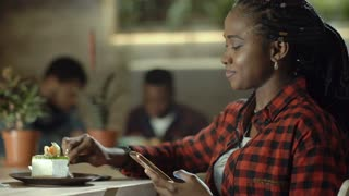 Relaxing black woman enjoying sweet dessert with coffee while surfing phone in cafeteria.