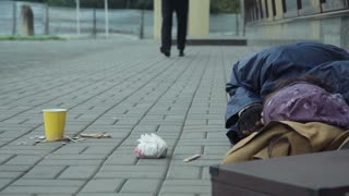 Rich man passerby giving money to sleeping homeless man