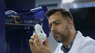 Scientific researcher holding and watching miniature of three-dimensional printed dinosaur skull in laboratory.